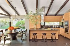 Basalt counters and floor tiles complement rift-cut teak cabinetry in the kitchen of John Legend's Los Angeles home.