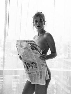 Nude woman reading newspaper