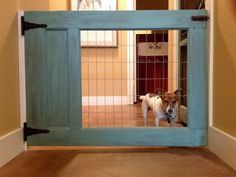 DIY doggie barrier: this nifty hallway gate is made from a simple wooden door sawn in half & the window replaced with sturdy wire mesh. Boom.