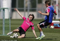 Fit-again Luka Modric (left) slides in to beat defender Fabio Coentrao to the ball in the Madrid sun