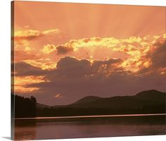 New York State, Adirondack Mountains, Rollins Pond, Sunlight and moody sky over the mountain and pond