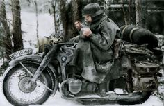 Kradmelder with BMW R12. A soldier might derive residual heat from the engine for a time after stopping to eat rations, sitting atop the BMW motorcycle, although even the motor appears to be frozen in this picture. 'Kradmelder' is the German for 'motorcycle messenger'.