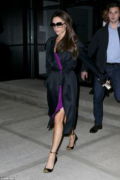 Victoria Beckham wearing a silk trench and violet slip dress from her own collection.