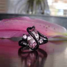 "🎉SALE!🎉 NWT The ""Bella"" Ring NWT Comes brand new with tag and free black velvet ring box.   Center Stone: 2.5ct Marquise Cut Lab Created Pink Sapphire Center Stone Dimensions: 14mm x 7mm. Side Stones: Pink Zircon Occasion: Christmas gift, anniversary, promise, party, costume, fun, or daily  Metals Type: 10k black gold filled mounting  Sizes available: 6.5, 7, 8, 9  *This is a NWT Retail item. Trades will not be considered in this closet. Meredith's Boutique Jewelry Rings"
