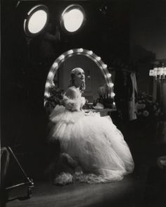 """Original caption: """"Carole Lombard, in her costume as """"Lily"""" in the first act of """"Twentieth Century"""" sits before her dressing room table at Columbia. Carole loves fresh flowers; two pots of them stand beside her mirror."""" Photo by: Irving Lippman"""