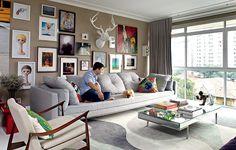 Tons de cinza e bege colorem a sala de estar. Na parede, a coleção de arte do empresário André Almada, que está ao lado de seu cão Guigo, da raça lulu-da-pomerânia