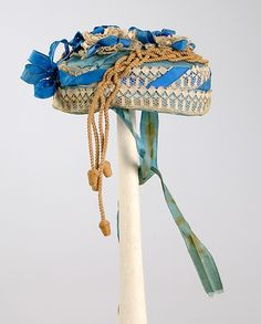 ca. 1865 hat of silk, linen, and straw (I presume the lace is linen and the acorn-terminated cords are straw). Met Museum.