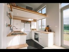 This tiny house in New Zealand is packed full of really unique features. From the sliding stairs case to the built-in sitting hammock in the living room.