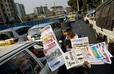 A vendor sells newspapers to motorists in Yangon, Myanmar on Monday.