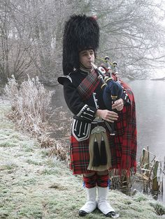 Piper playing the Great Highland Bagpipes, in traditional Scottish piper's uniform.