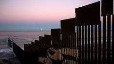 """In Tijuana, Mexico, the fence stretches into the Pacific Ocean. On November 14, 2016, a """"supermoon"""" set behind the US-Mexico border fence during its closest orbit to Earth since 1948."""