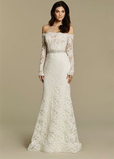 Ivory Alencon lace sheath bridal gown, off the shoulder overlay with a sweetheart neckline and long sleeves, encrusted belt at the natural waist, scooped illusion back and chapel train.