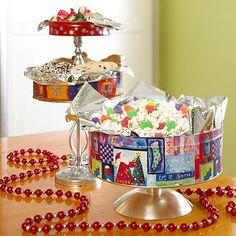 use old Christmas tins as serving pieces by using large glue dots to adhere tins to the tops of candlesticks