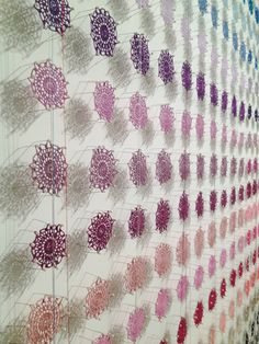 1000 handmade doilies by Lisa Solomon. Could wrap thread around some nails in the shape of a cog.