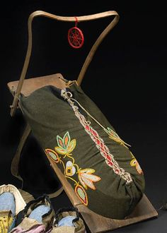 """An Ojibwa beaded cradleboard • Made of a wood backboard with double-curved projection at top, attaching a cloth pouch laced up the front and decorated with a floral design, a """"spider web"""" talisman hanging at top. length 28 1/2in Provenance: B W Thayer Collection; an attached note from Thayer describes the construction of the cradle, how it was used, and where it was collected: """"...Bot (sic) in 1932 from Mrs. George Norcross formerly Miss Josephine Lightning, born 1890 of Ponsford on White…"""