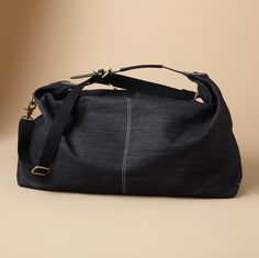 """Freeform (the better to stuff it with a day's worth of necessities) cotton denim shapes an ideal getaway bag, equipped with an adjustable black webbing strap and zip top. Lined, with one pocket. Imported. 24-1/2""""W x 6-1/2""""D x 14""""H."""