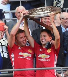 Michael Carrick and Ander Herrera of Manchester United lift the Community Shield trophy after the FA Community Shield match between Leicester City...