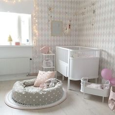A soft neutral nursery with a beautiful feature wall behind the crib. The doll bed beside the crib is adorable and the little cushion in the middle is such a cozy space to read books!