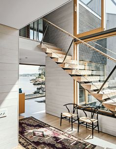 Modern Connecticut summer home renovation with white cedar paneling, glass windows by Town & Country Glass in the entry and ash risers on the stairs