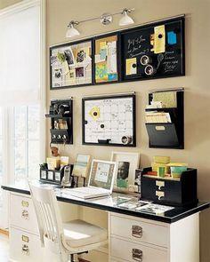 Escritorio organizado con repisas y pizarras en la pared y pequeños cajones y porta lápices sobre la mesa del escritorio. Todo en tonos blanco y negro.