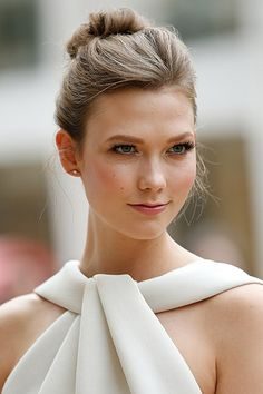 Karlie Kloss Best Beauty Moments | This may be the most elegant moment we've seen from Karlie yet! She channels ethereal sophistication in a loose ballerina bun and pretty pink cheek. Her brows are filled in a touch more than usual, anchoring her light eye makeup and long lashes.