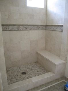 Showers - Beautiful Travertine shower with accents of Maluka Tan pebbles.  The stone moldings and bathroom floor are Seagrass Limestone.
