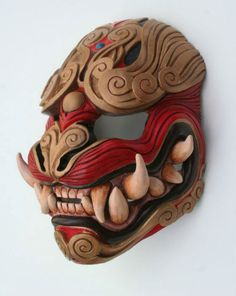 Japanese Demon Oni mask made out of wood and red and brown.