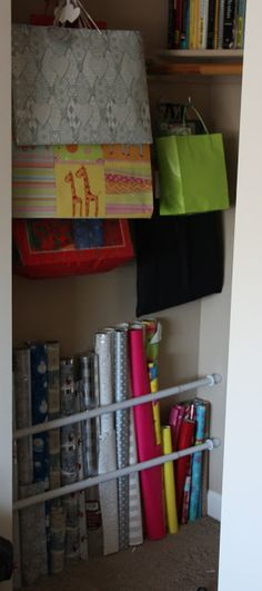 thelovebugsblog.blogspot.ca - gift wrap storage in closet, tension rods to hold wrapping paper, hooks for bags