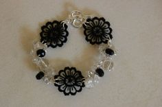Onyx Flower Bracelet - ML63B  Glamorous bracelet with clear Czech crystals, black onyx cut stones, glass beads, and black lace flowers. Wear it to a fancy event or on a night out. Black onyx is the stone of self mastery and self control. Silver-plated heart lock. Crocheted with metallic silver thread.  $54.00  http://www.melissajewelrydesign.com/bracelets/onyx-flower-bracelet