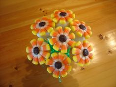 Chocolate/peanut butter cake pops dippen in white candy melts.  Candy corn for petals  chocolate icing center