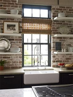 Brick wall, tall window, floating shelves, and a farm sink.  The only way to make it better would be adding butcher block counters.