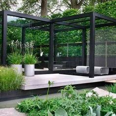 A modernized black pergola works well with the greenery. The light floors of the pergola create a a different level of living space within the garden.