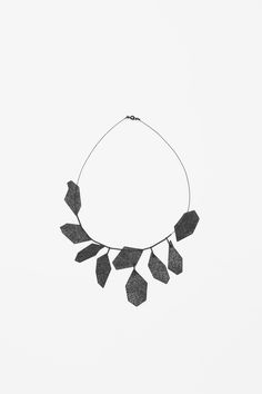 COS. Set on a fine metal wire, this necklace has angular pendants with a modern laser cut design