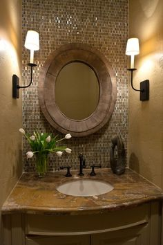 Love the shimmery tile wall with matte wood mirror.  Interesting how (and where) the sconces are hung.