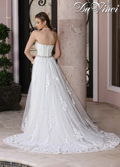 Tulle and lace sweetheart strapless gown with beaded trim along natural waistline. Lace appliques are placed throughout this flowing tulle skirt and accented with a beautiful hem lace.  Zipper back