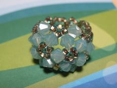 This is a classic beaded ring pattern. Looks great in monochromatic color scheme.   Materials: 15 4mm bicone crystal beads (Pacific Opal)...