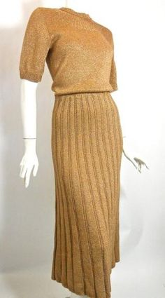 """1930s bronze metallic knit dress   with deco sunburst neckline and   ribbed skirt. Side metal zipper and   metal zipper to left side of neckline   across shoulder. No label, no flaws,   elastic band at waist within dress.   Click picture for more images.  38"""" bust, 28"""" waist, 42"""" hips, 50""""   long"""