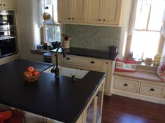 Island w/farmhouse sink across from induction cooktop.