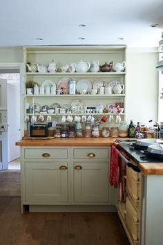 Une commode traditionnelle galloise peinte en vert expose une collection de vaisselles vintage dans  la cuisine d'un cottage anglais. Jonathan Gooch Photographer. (Houzz- Brook Cottage)