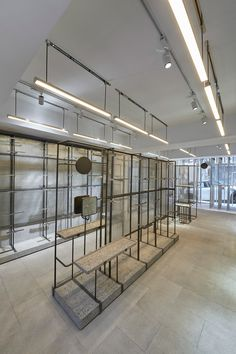 Set inside a double-height space in the Sheung Wan area of Hong Kong, the store has a facade that features rows of vertically-arranged steel poles stretching across both levels.