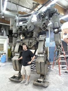 Stan Winston Studio/Legacy Effects master painter, Trevor L. Hensley poses with AVATAR's full-size AMP suit.