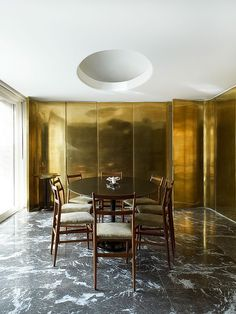 parede metalizada e piso de mármore preto em sala de jantar