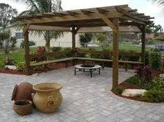 A pergola affords an outside room to relax in - surrounded by low walls and beautifully tended flower beds.