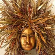 Mask spray painted gold, glued to a styrofoam block and then a wonderous collection of dried wheat, cattails, grasses and corn