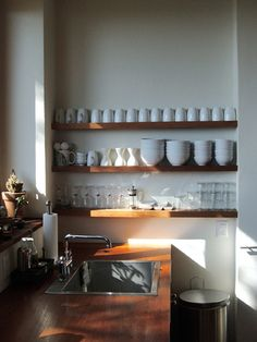 wide wooden shelves and white china
