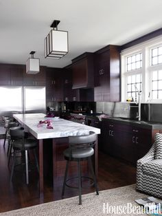 mahogany is used extensively in the kitchen of shingle style long island beach house decorated