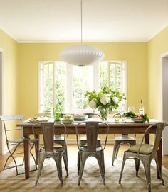 In this photo:  injected modern touches, such as the George Nelson-designed globe lamp that hangs above their farm table and raw-steel chairs from Sundance.   - CountryLiving.com