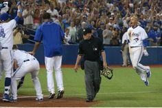 The Jays mob Ryan Goins, right, at home plate after his 10th-inning walkoff homer run that gave Toronto a 5-3 victory over the Indians Tuesday night.