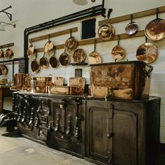 Copper pots and pans hang from the wall above the cooking range at the kitchen at Lanhydrock in Cornwall.