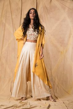 Ivory muga tussar crop top and palazzo pants layered with a mustard muga tussar cape, hand-embroidered with zardozi and thread.
